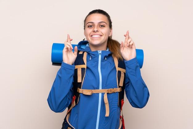 Молодая девушка альпиниста с большим рюкзаком с скрещиванием пальцев