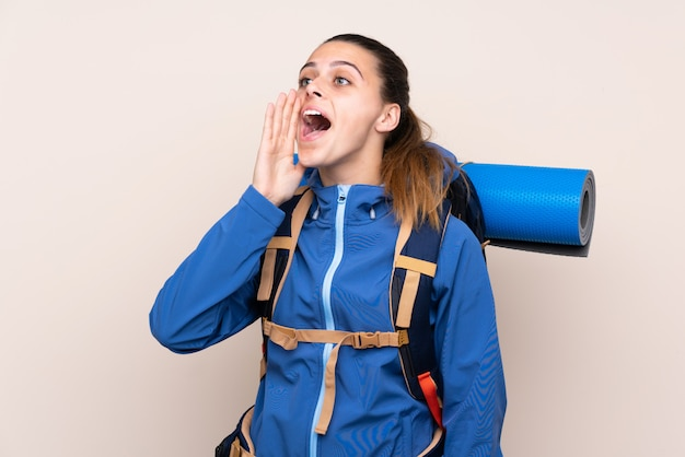 Молодая альпинистка с большим рюкзаком кричит с широко открытым ртом