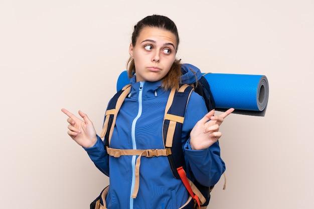 疑いのある側面を指している大きなバックパックを持つ登山少女