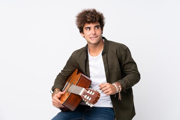 ギターの疑いを持つ分離白と混乱の表情を持つ若い白人男