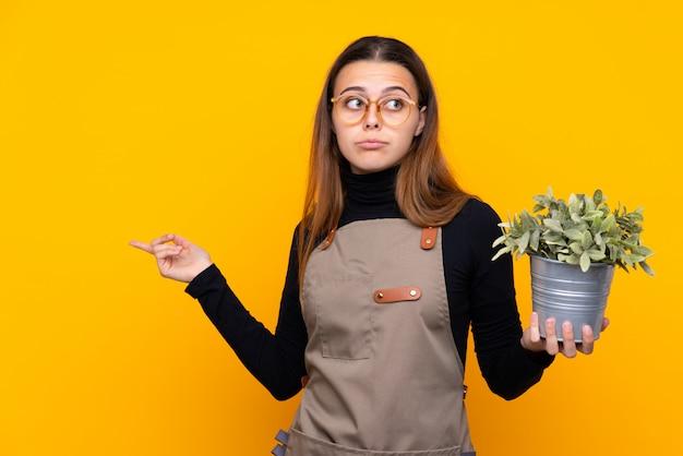 疑いのある側面を指している植物を保持している若い庭師の女の子