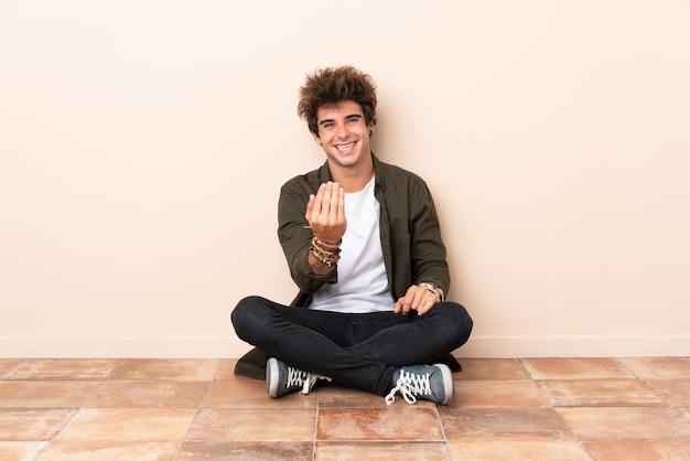 手に来るように招待して床に座っている若い白人男。あなたが来て幸せ