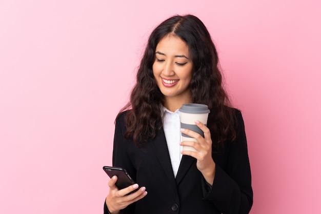 混血ビジネス女性がコーヒーを奪うと電話を保持