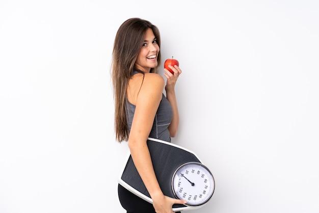 Подросток бразильская девушка держит весы с весами и с яблоком
