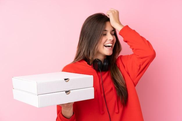 孤立したピンクの壁にピザの箱を置くブラジルのティーンエイジャーの女の子は、何かを実現し、解決策を意図