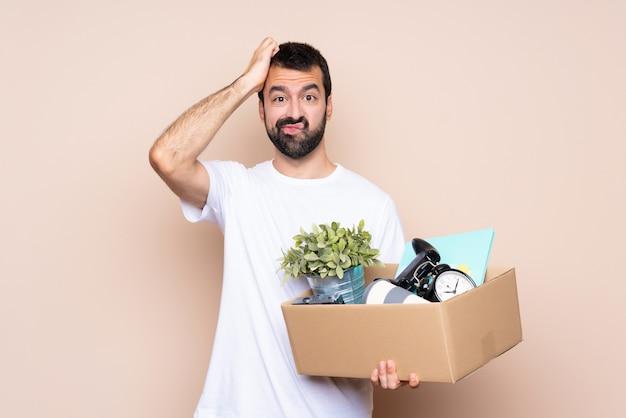 箱を持って、欲求不満の表現と理解していない新しい家に移動する男