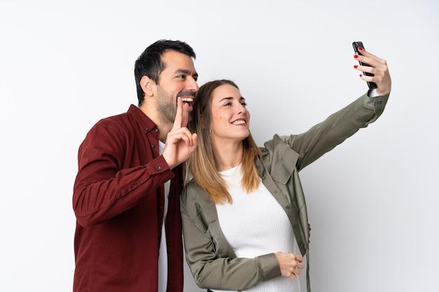 Пара в день святого валентина на изолированной стене делает селфи с мобильным телефоном