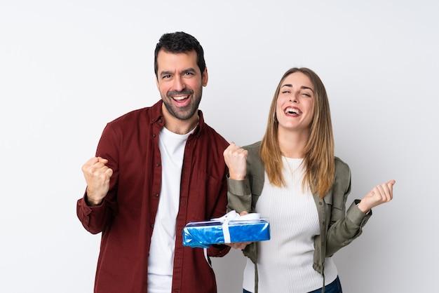 勝者の位置で勝利を祝う孤立した壁を越えて贈り物を保持しているバレンタインの日のカップル