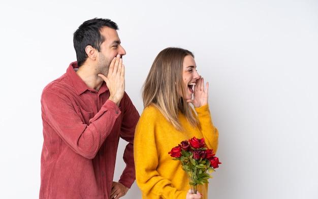 Пара в день святого валентина, держащая цветы по изолированной стене, кричащей с широко открытым ртом к боковой стороне