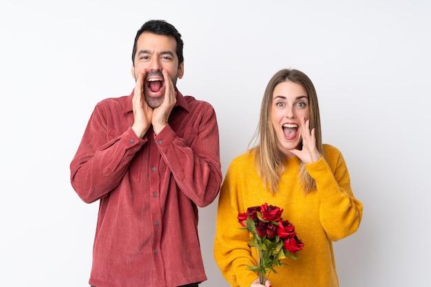 Пара в день святого валентина, держащая цветы по изолированной стене, кричащей и объявляющей что-то