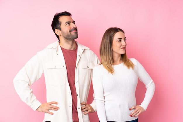 Пара в день святого валентина над розовой стеной позирует с руки на бедра и смеется