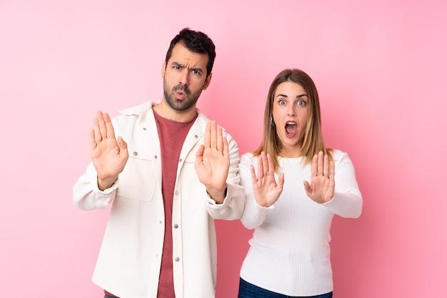 Пара в день святого валентина на изолированной розовой стене делает жест остановки для разочарованного мнения