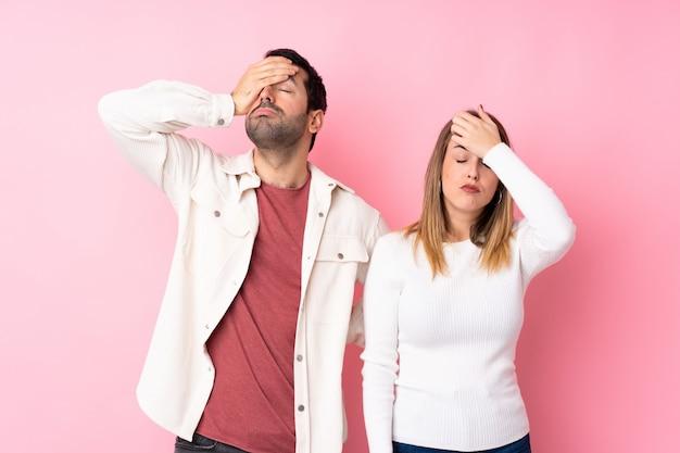 驚きとショックを受けた表情で分離されたピンクの壁の上のバレンタインの日のカップル