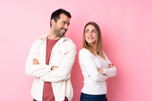 笑顔で肩越しに見ている分離のピンクの壁の上のバレンタインの日のカップル