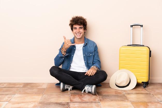 床に座ってスーツケースを持つ旅行者男