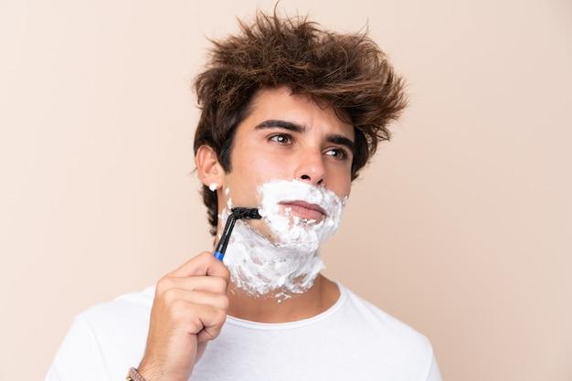 Молодой красавец брить бороду