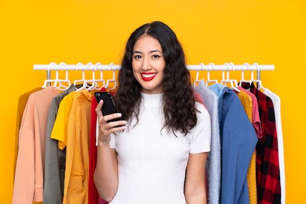 衣料品店の女性と携帯電話で話しています。