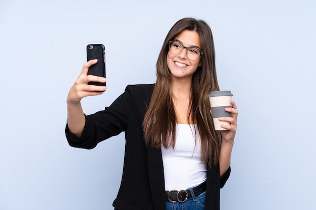 奪うためにコーヒーを保持している若いビジネス女性