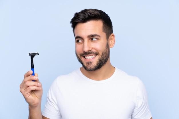 Человек с лезвием над изолированной синей стеной