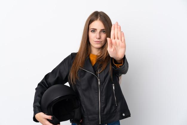 Женщина с мотоциклетным шлемом над изолированной стеной