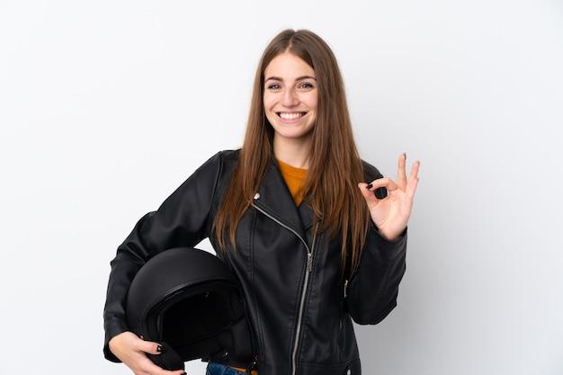 孤立した壁の上のオートバイのヘルメットを持つ女性