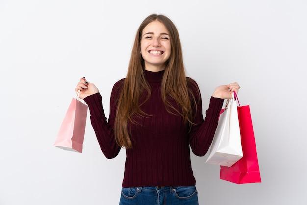 孤立した白い壁の上の買い物袋を持つ女性