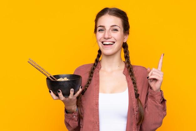 Девочка ест лапшу на изолированной желтой стене