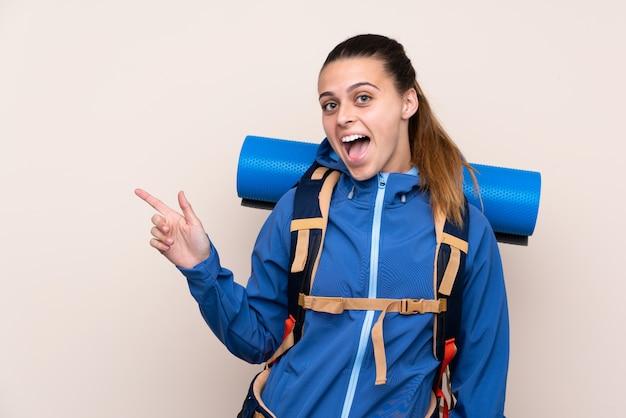 Девушка с рюкзаком альпиниста над изолированной стеной
