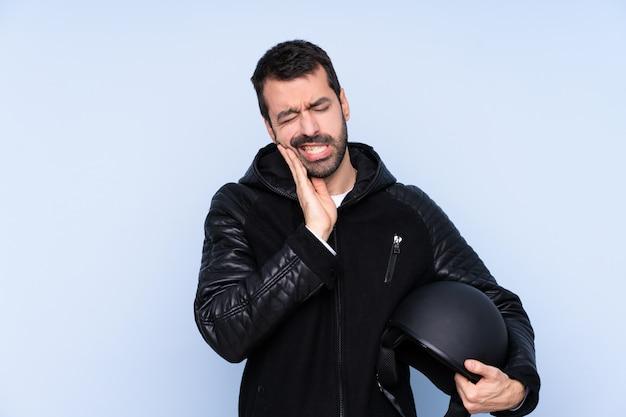 Человек с мотоциклетным шлемом над изолированной стеной