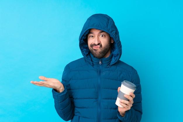 孤立した壁の上の冬のコートを持つ男