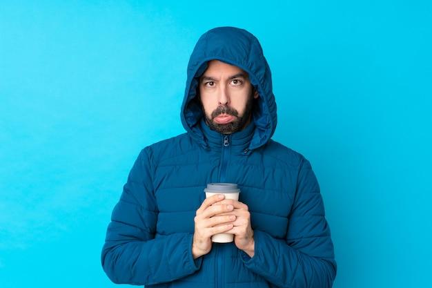 Человек с зимним пальто на изолированной стене