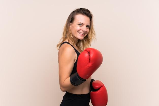 孤立した壁の上の若いスポーツ女性