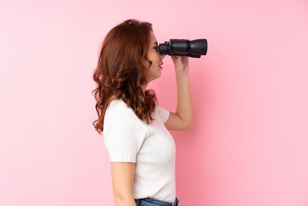 孤立したピンクの壁の上の若い女性