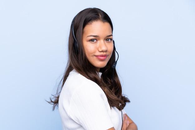 孤立した壁の上の若いテレマーケティング女性
