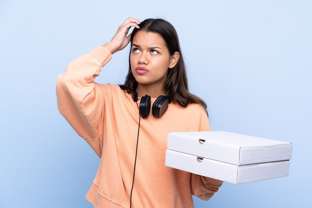 Девушка ловит коробки для пиццы на изолированной стене