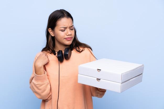 孤立した壁の上のピザの箱を引く女の子