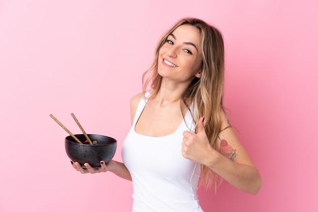 箸で麺のボウルを押しながら何か良いことが起こったので、親指で孤立したピンクの壁の上の若い女性
