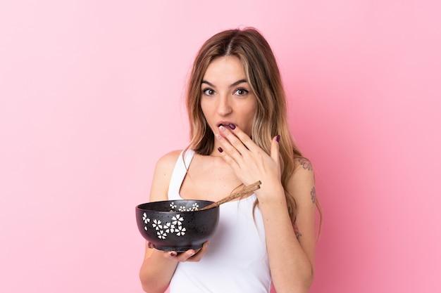 Молодая женщина над изолированной розовой стеной держит миску лапши с палочками и удивлен