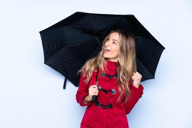 冬のコートと勝利を祝って傘を保持している若い女性