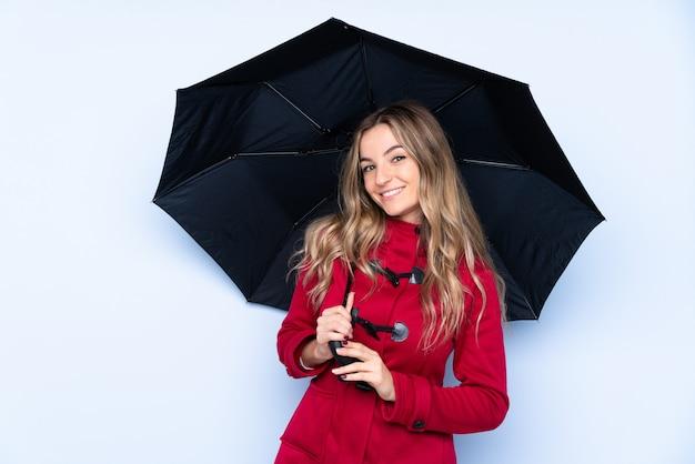 Молодая женщина с зимним пальто и проведение зонтик с счастливым выражением