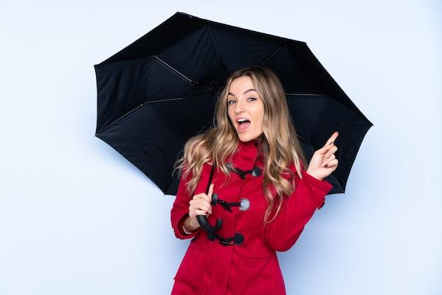 Молодая женщина с зимним пальто и проведение зонтик удивлен и указывая пальцем в сторону