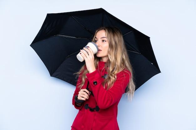 傘と持ち帰るコーヒーを保持している冬のコートを持つ若い女性