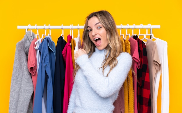 勝利を祝う孤立した黄色の壁の上の衣料品店の若い女性