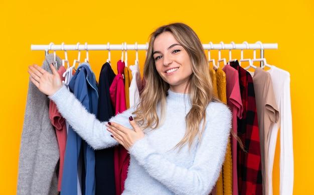 来て招待する側に手を拡張する孤立した黄色の壁の上の衣料品店の若い女性