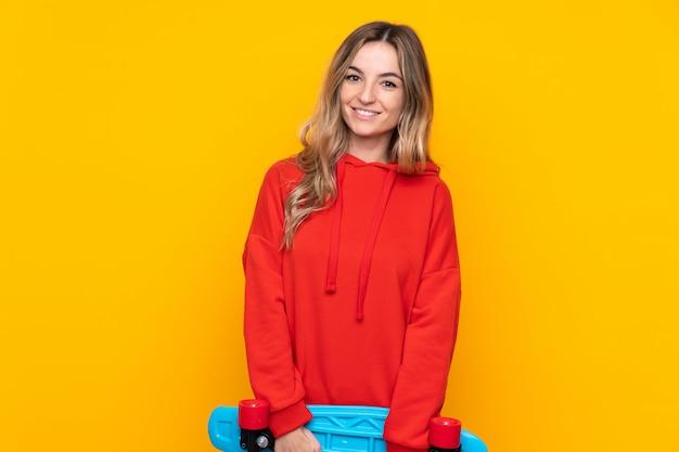 幸せな表情でスケートで孤立した黄色の壁の上の若い女性
