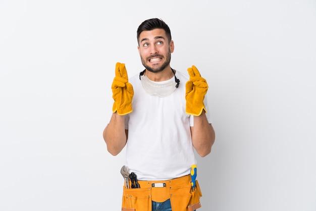 Ремесленники или электрик человек над изолированной белой стене с пересечением пальцев