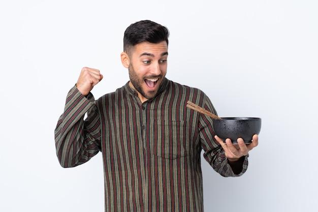 箸で麺のボウルを押しながら勝利を祝って孤立した壁の上の若い男
