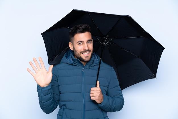幸せな表情で手で敬礼分離壁に傘を保持している男