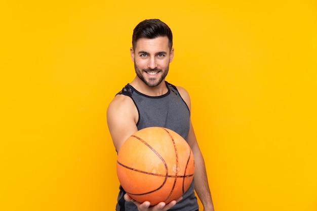 Человек над изолированной желтой стеной играет в баскетбол
