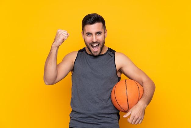 勝利を祝う孤立した白い壁の上のハンサムな若いバスケットボールプレーヤー男